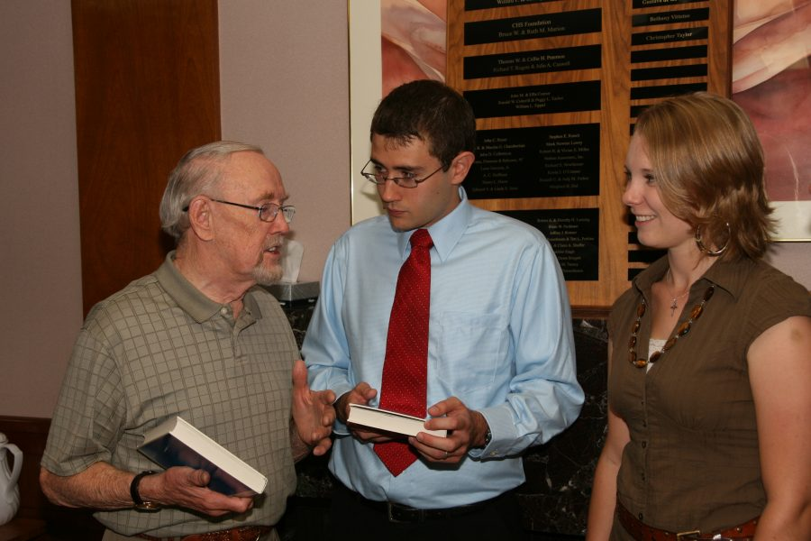 professor presenting book to two students